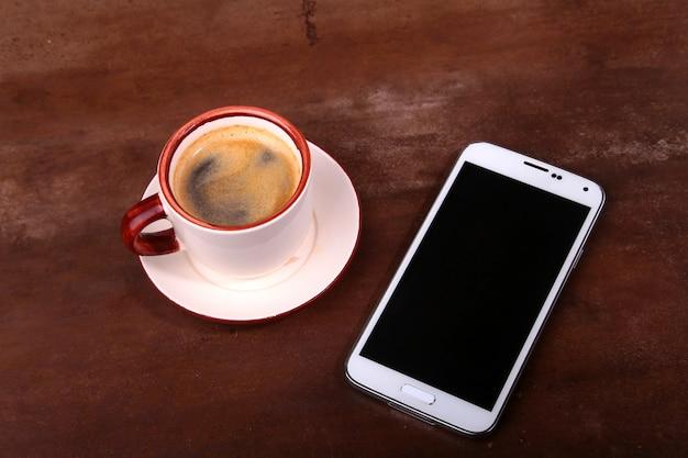 Filiżanka kawy i smartphone na drewnianym stole.