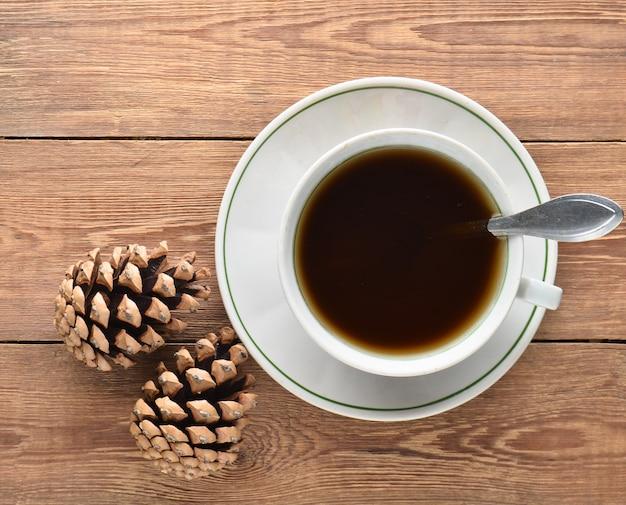 Filiżanka kawy i sosna rożki na drewnianym stole. świąteczny poranek.