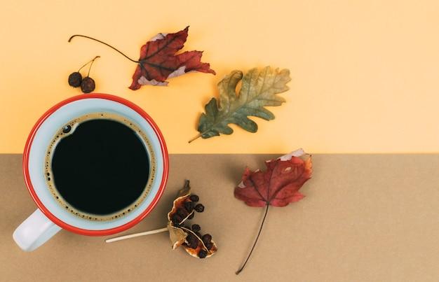 Filiżanka kawy i suszonych liści na pomarańczowo i brązowo