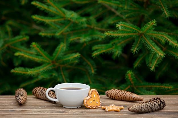 Filiżanka kawy i świąteczne pierniki na drewnianym stole z gałęzi świerkowych na tle