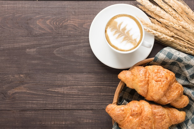 Filiżanka kawy i świeże pieczone rogaliki na drewnianym stole. widok z góry