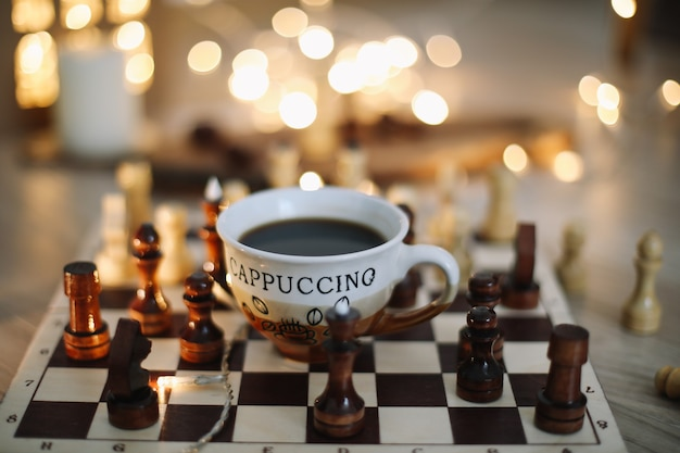 Filiżanka kawy i szachy na szachownicy koncepcja gry hobby przerwa na kawę