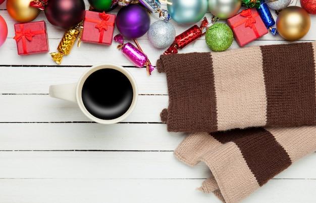 Filiżanka kawy i szalik z świątecznymi zabawkami.