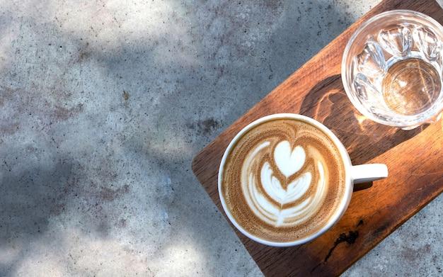 Filiżanka kawy i szklanka wody na betonowym stole w cieniu drzewa.
