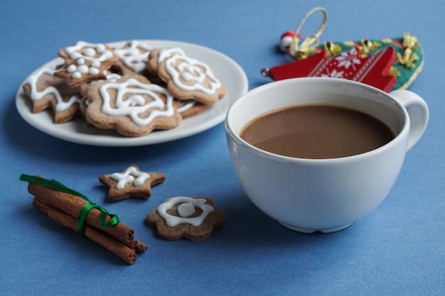 Filiżanka kawy i talerz świątecznych imbirowych herbatników z polewą z białego cukru