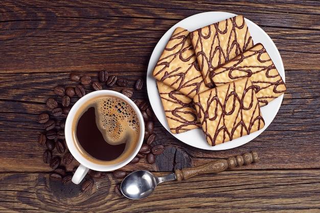Filiżanka kawy i talerz z kwadratowymi czekoladowymi ciasteczkami na ciemnym drewnianym stole, widok z góry