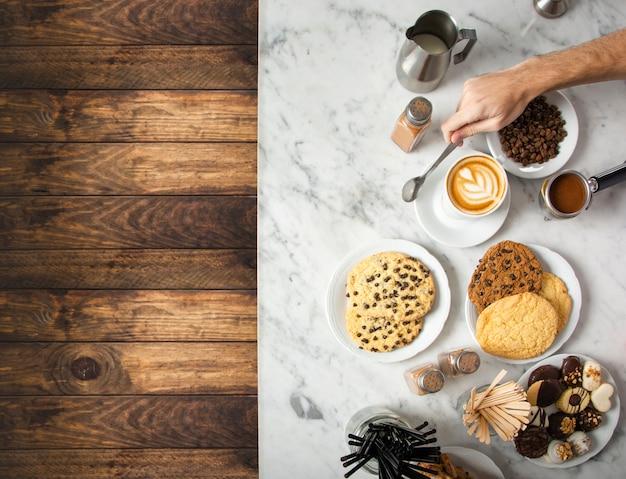 Filiżanka kawy i talerze z czekoladowymi ciasteczkami