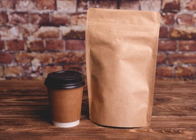 Filiżanka kawy i torebka z papieru rzemieślniczego na drewnianym stole przy ścianie z cegły