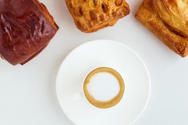 Filiżanka kawy i trzy bułeczki na białym tle. widok z góry płaski