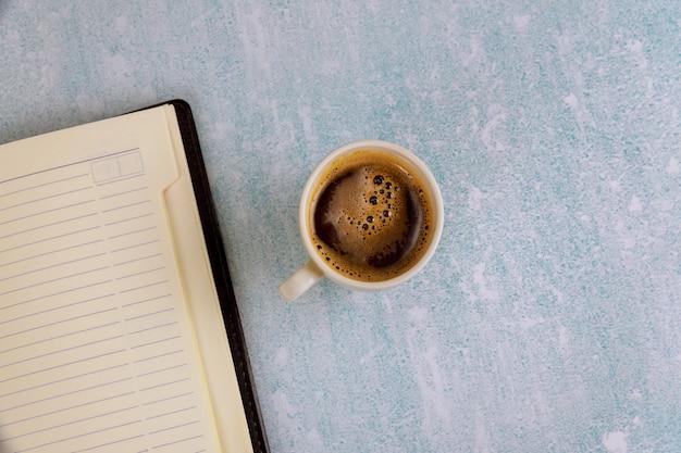 Filiżanka kawy i tygodniowy notatnik z planowaniem i projektowaniem do biurka z góry