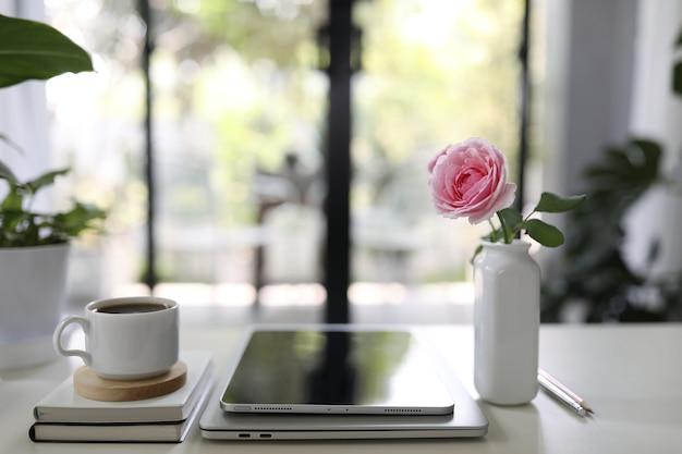 Filiżanka kawy i wazon róży z tabletem na drewnianym stole w pomieszczeniu