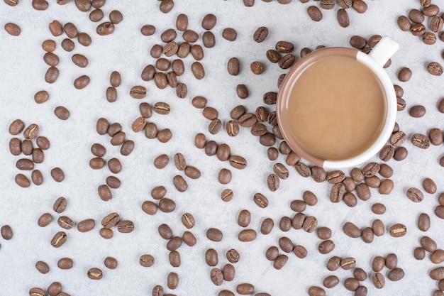 Filiżanka kawy i ziaren kawy na marmurowym tle. zdjęcie wysokiej jakości