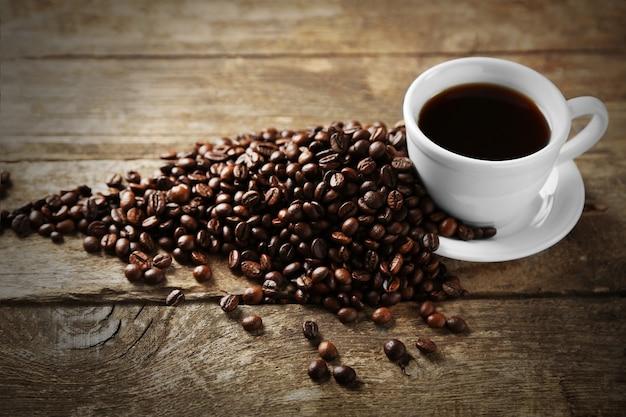 Filiżanka kawy i ziaren kawy na powierzchni drewnianych