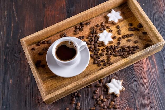 Filiżanka kawy i ziaren kawy w drewnianej tacy