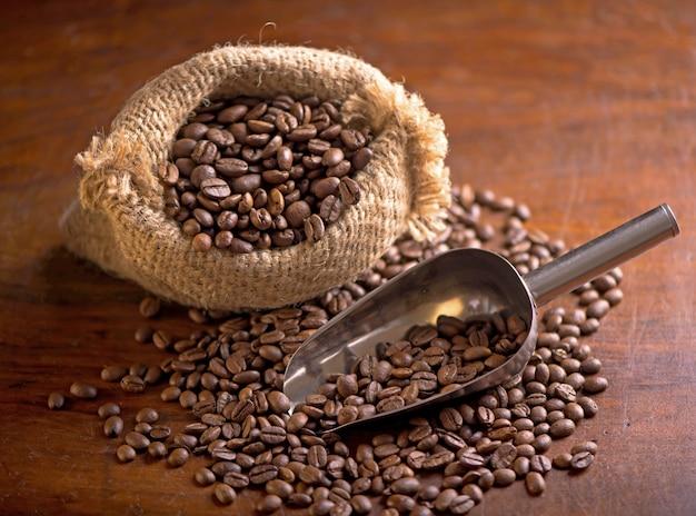 Filiżanka kawy i ziaren kawy w worku na ciemnym tle, widok z góry