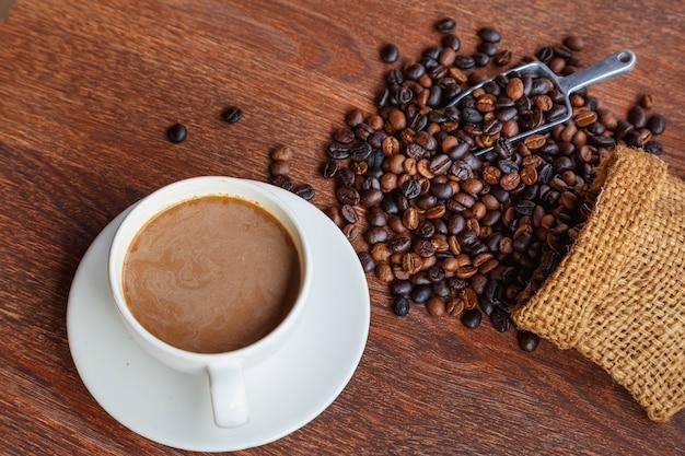 Filiżanka kawy i ziaren kawy w worku, widok z góry