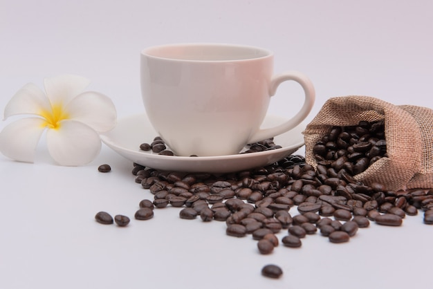 Filiżanka kawy i ziarna kawy na białym stole z kwiatem plumeria