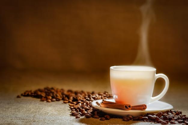 Filiżanka kawy i ziarna kawy na drewnianym stole i worek