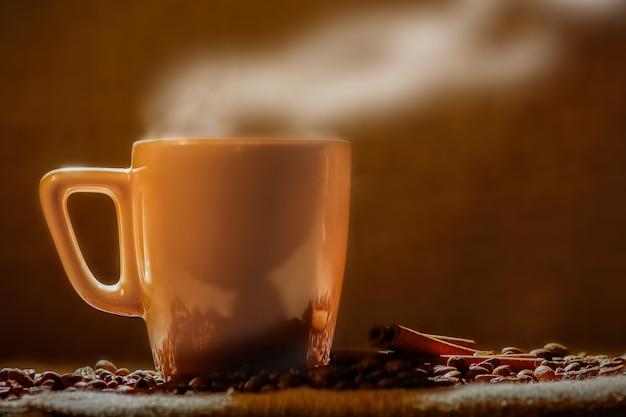 Filiżanka kawy i ziarna kawy na drewnianym stole i worku