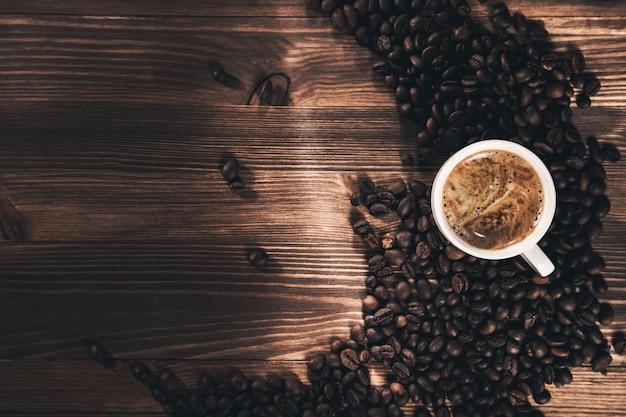 Filiżanka kawy i ziarna kawy na drewnianym tle.