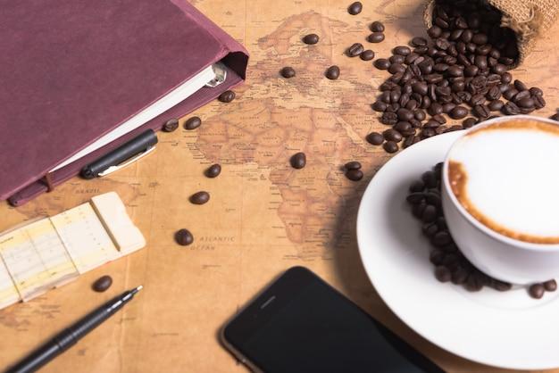 Filiżanka kawy i ziarna kawy na stole z dużym tle mapy na tabulatorze