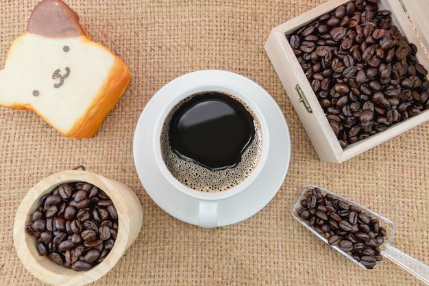 Filiżanka kawy i ziarna kawy na szorstkim worku