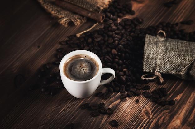 Filiżanka kawy i ziarna kawy na tle tkaniny worek.