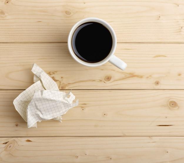 Filiżanka kawy i zmięty papier na drewnianym stole