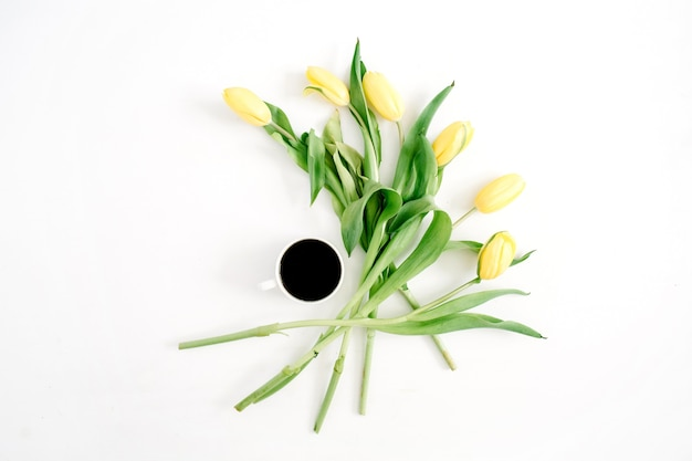 Filiżanka kawy i żółte kwiaty tulipanów na białym tle