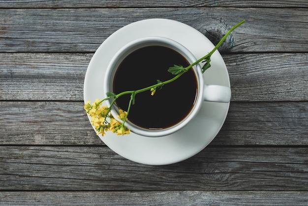 Filiżanka kawy i żółty kwiat na drewnianym stole, strzał na stole