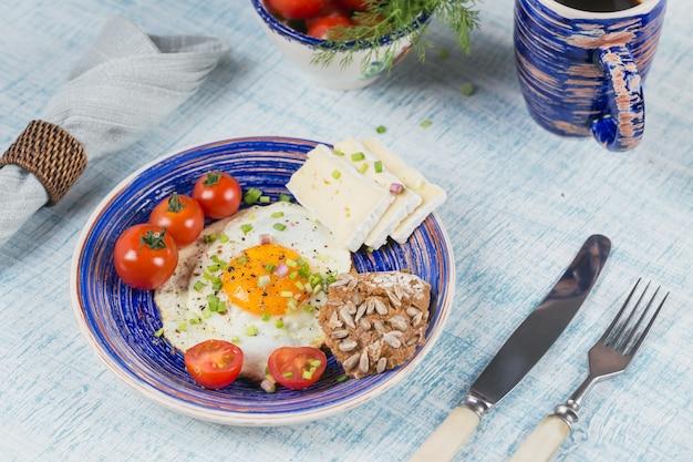 Filiżanka kawy, jedno jajko, ser i pomidorki koktajlowe na zdrowe śniadanie.