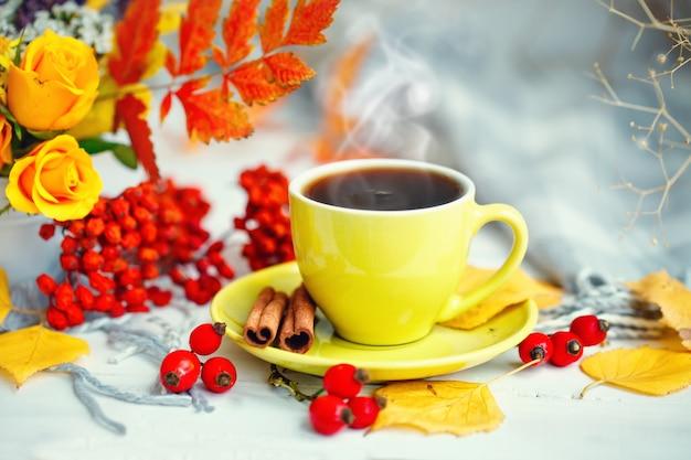 Filiżanka kawy, jesień liście i kwiaty na drewnianym stole