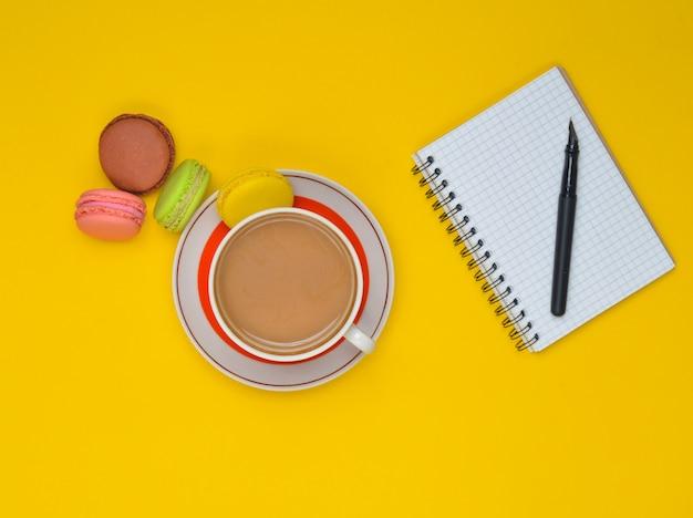 Filiżanka kawy, kolorowe makaroniki, notatnik z piórem na tle.