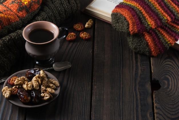 Filiżanka kawy, książka, czapka z dzianiny i rękawiczki na drewnianym stole