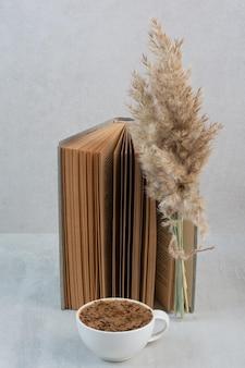Filiżanka kawy, książka i roślina na szarym stole. zdjęcie wysokiej jakości