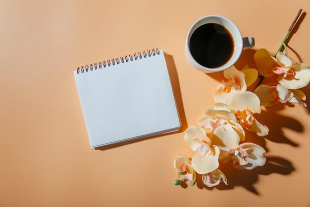 Filiżanka kawy kwiaty i notatnik w tle