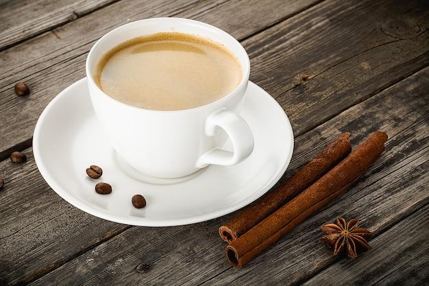 Filiżanka kawy laski cynamonu i anyż gwiazda na starym drewnianym stole.