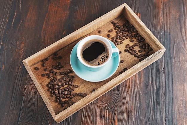 Filiżanka kawy latte art i pobliskich ziaren kawy w drewnianym pudełku na ciemnym tle drewnianych.