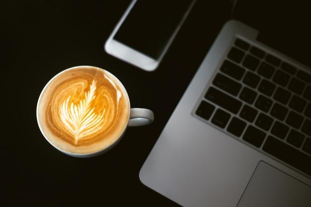 Filiżanka kawy latte art, smartphone i tablat