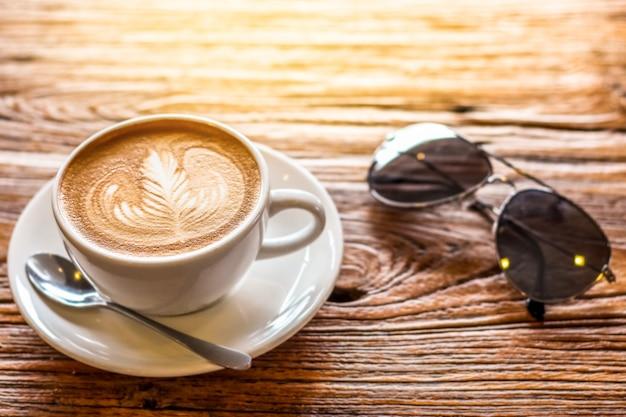 Filiżanka kawy latte art z łyżką i talerz na brązowej kory piękne tekstury tła z ciepłym światłem ozdobione okularami przeciwsłonecznymi