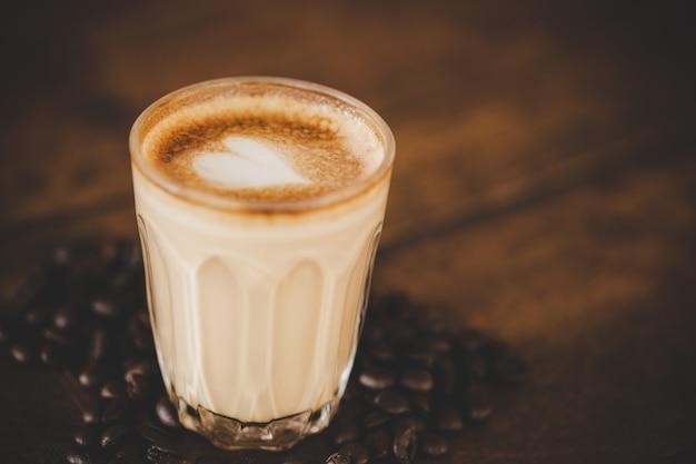 Filiżanka kawy latte na stół z drewna w kawiarni kawiarni