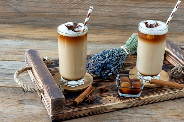 Filiżanka kawy latte z domowym syropem lawendowym i kwiatami na drewnianej tacy. przytulne śniadanie.