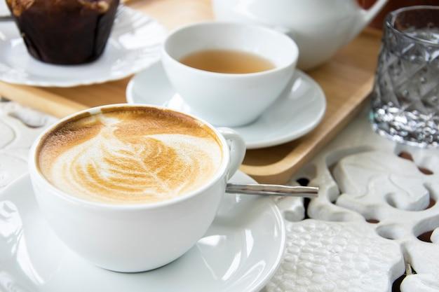 Filiżanka kawy latte z herbatą i babeczkami. poranna kawa biały ton.