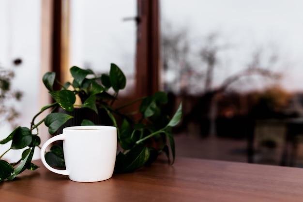 Filiżanka kawy lub herbaty na stole na drewnianym brązowym tarasie podczas wieczornego zachodu słońca. relaks, cicha koncepcja życia na wsi