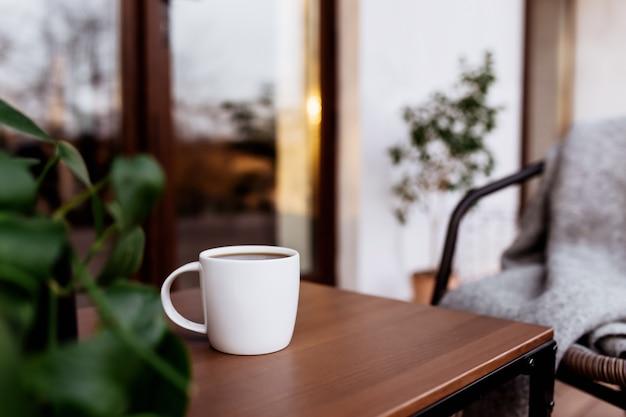Filiżanka kawy lub herbaty na stole na drewnianym brązowym tarasie podczas zachodu słońca. relaks, cicha koncepcja życia na wsi