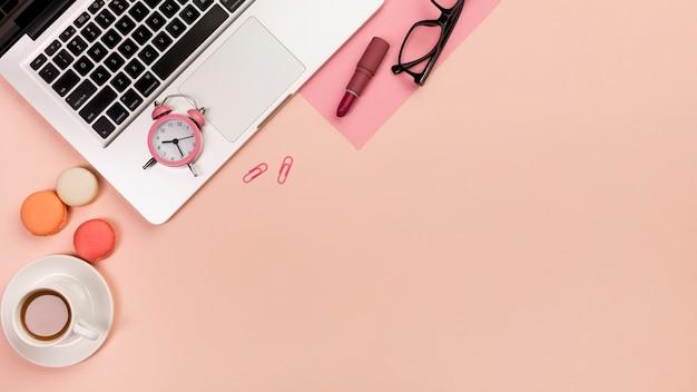 Filiżanka kawy, makaroniki, budzik, laptop, okulary i szminka na tle brzoskwini