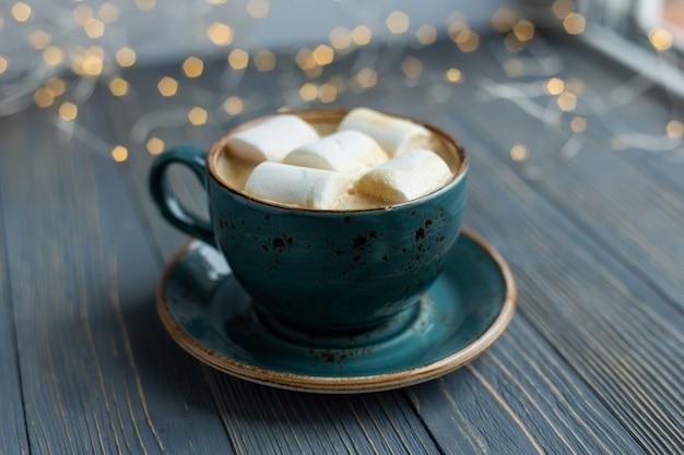 Filiżanka kawy, marshmallow na drewnie