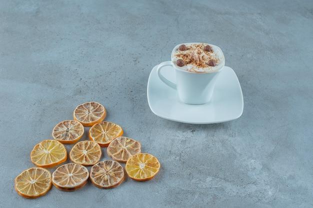 Filiżanka kawy mlecznej obok plasterków cytryny, na niebieskim tle.