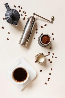 Filiżanka kawy, młyn do kawy, dzbanek do kawy i śmietanka ze śmietaną na stole