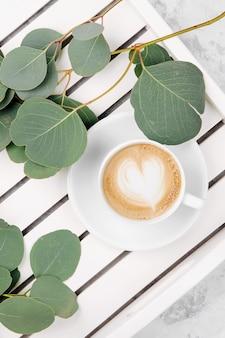 Filiżanka kawy na białej drewnianej tacy do serwowania i gałęzi eukaliptusa